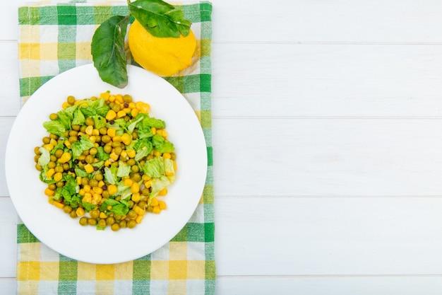 Vista superior de ensalada de maíz y limón sobre tela y superficie de madera con espacio de copia