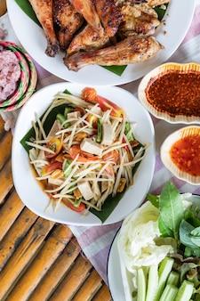 Vista superior de la ensalada de papaya y pollo a la parrilla en un plato blanco sobre fondo de bambú