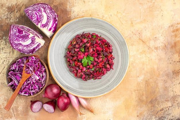 Vista superior ensalada de remolacha fresca aderezada con perejil en un plato hecho de cebollas rojas, repollo y otras verduras sobre un fondo de madera con espacio de copia a la derecha