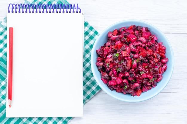 Vista superior de la ensalada de remolacha en rodajas con verduras dentro de la placa azul con el bloc de notas en el escritorio de luz, ensalada de vegetales, vitamina, comida, salud