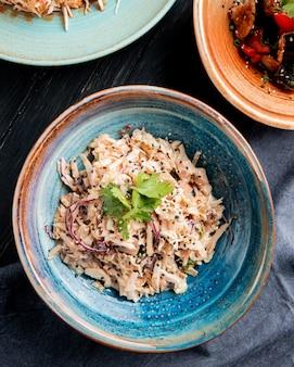 Vista superior de ensalada con repollo picado pollo y semillas negras en un plato sobre superficie de madera