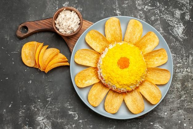 Vista superior de la ensalada en el soporte de la placa con un tazón de queso y papas fritas en el costado sobre fondo gris oscuro