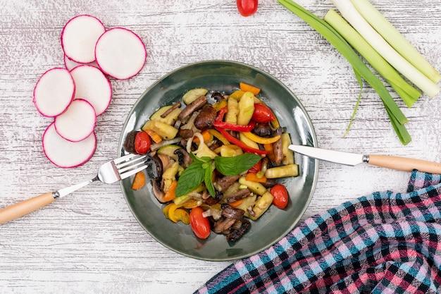 Vista superior ensalada de vegetales fritos seta tomate cherry pimiento rojo pimiento amarillo con cuchillo y tenedor