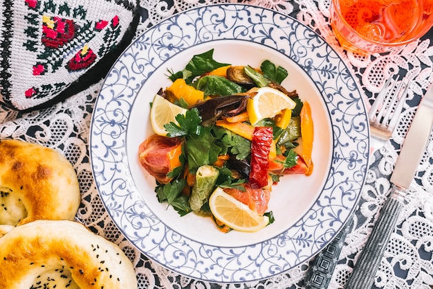 Vista superior de ensalada de vegetales salteados con pimientos berenjena tomate hierbas y limón
