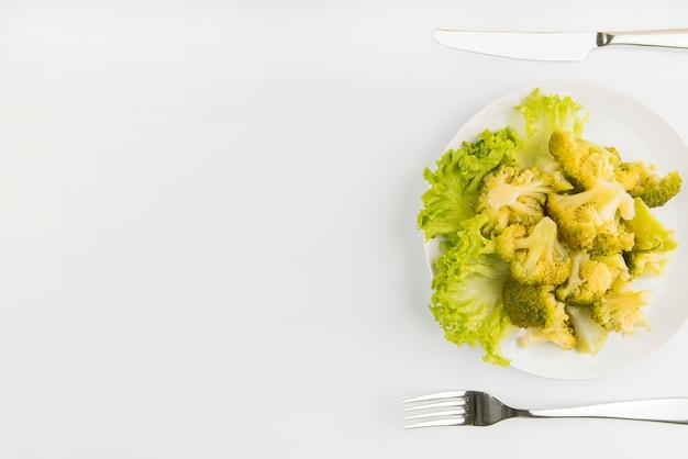 Vista superior ensalada verde con cubiertos y espacio de copia