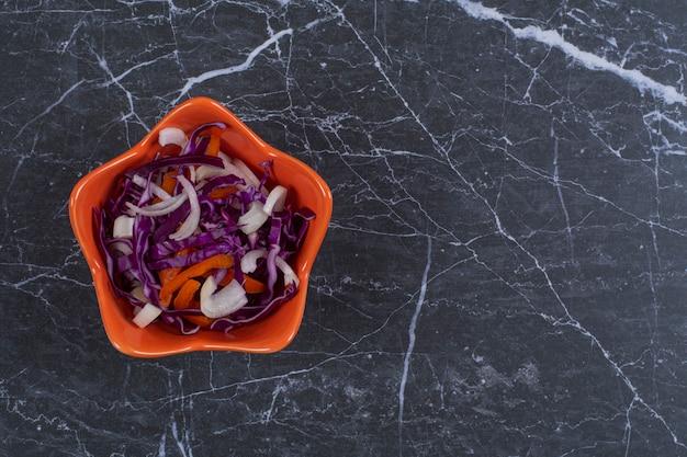 Vista superior de ensalada de verduras frescas en un tazón de naranja.