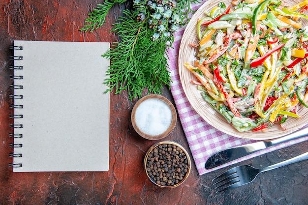 Vista superior de ensalada de verduras en un plato sobre un mantel, tenedor y cuchillo, sal y pimienta negra, un cuaderno en la mesa de color rojo oscuro