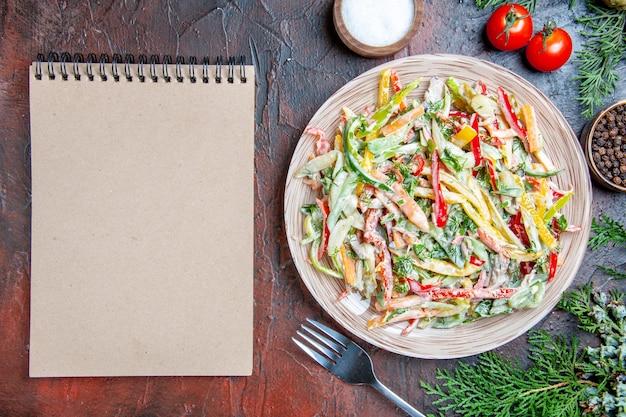 Vista superior ensalada de verduras en plato tenedor tomates ramas de pino bloc de notas especias en mesa rojo oscuro