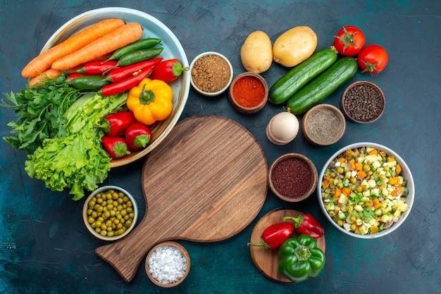 Vista superior de ensalada de verduras en rodajas aderezado con rodajas de pollo dentro de la placa con verduras frescas en el escritorio azul, almuerzo, ensalada, comida vegetal