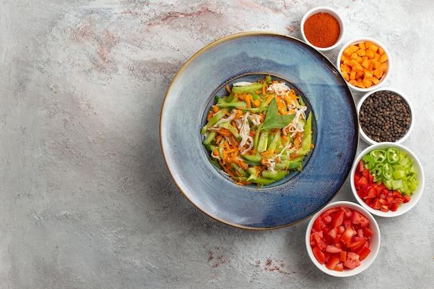 Vista superior de ensalada de verduras en rodajas con condimentos sobre fondo blanco.