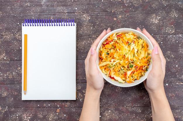 Vista superior ensalada de verduras en rodajas fresca y salada dentro del plato sostenido por la hembra con el bloc de notas en el escritorio marrón comida vegetal plato de comida foto fresca