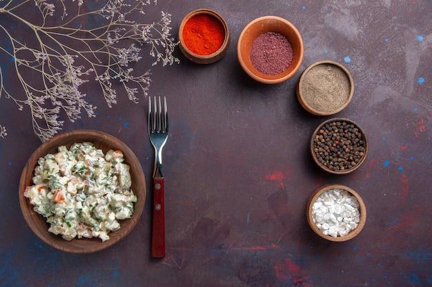 Vista superior de ensalada de verduras en rodajas con mayyonaise y pollo junto con condimentos sobre fondo oscuro comida ensalada comida merienda almuerzo
