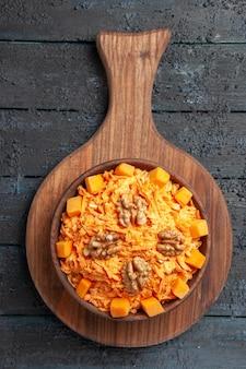 Vista superior ensalada de zanahoria fresca ensalada rallada con nueces en el escritorio oscuro ensalada de dieta color nuez salud