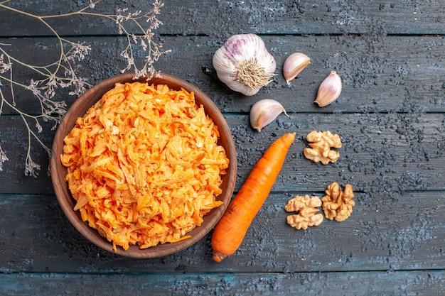 Vista superior ensalada de zanahoria rallada con ajo dentro de la placa en el escritorio rústico azul oscuro ensalada de salud dieta de color de verduras maduras
