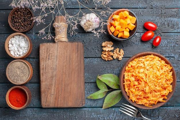 Vista superior ensalada de zanahoria rallada con ajo, nueces y condimentos en el escritorio oscuro ensalada de dieta saludable color naranja maduro