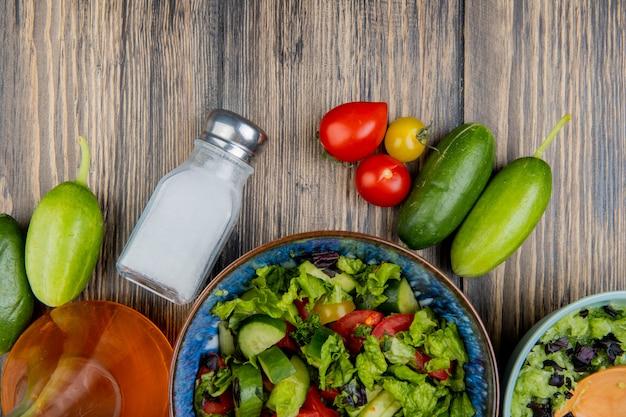Vista superior de ensaladas de verduras con tomate, pepino, aceite derretido y sal sobre madera