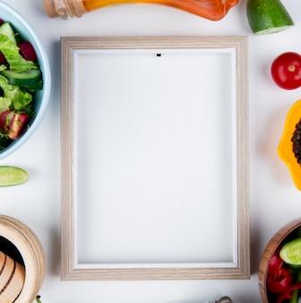 Vista superior de ensaladas de verduras y verduras como tomate pepino con mantequilla derretida pimienta negra y marco sobre superficie blanca con espacio de copia