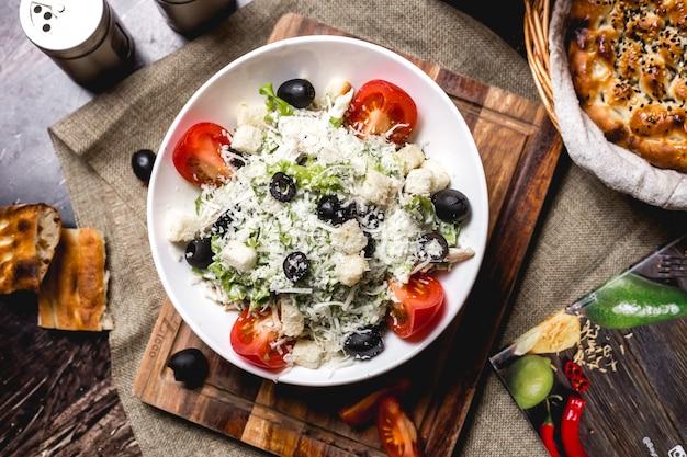 Vista superior de la ensaladera césar adornada con queso rallado y aceituna