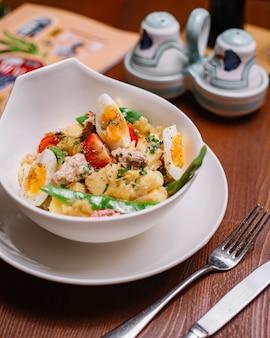 Vista superior de la ensaladera de papa italiana con atún frijoles perejil tomate cherry huevos cocidos y aceite de oliva