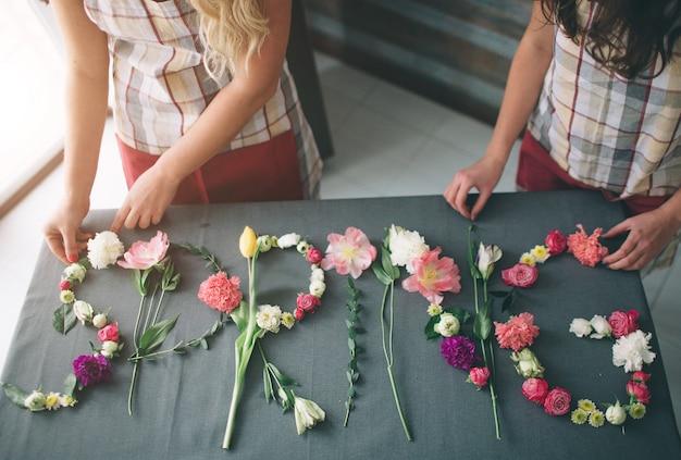 Vista superior de la entrega de flores. floristas creatin palabra primavera de flores en el fondo. concepto de primavera. lay flat