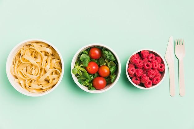 Vista superior de envases de alimentos con frambuesas, ensalada y pasta.