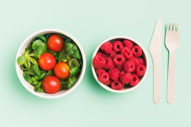 Vista superior de envases de alimentos con frambuesas y ensalada