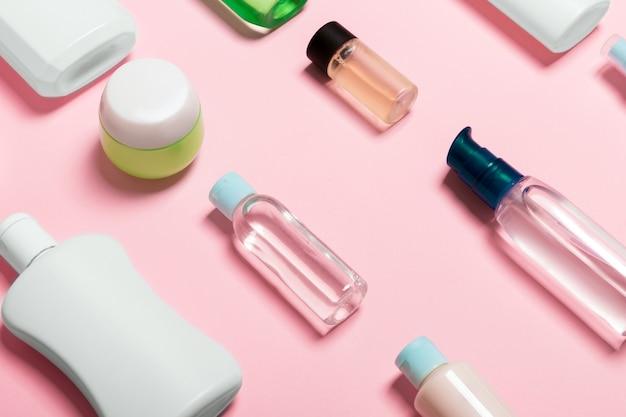 Vista superior de envases cosméticos, aerosoles, frascos y botellas sobre fondo rosa.