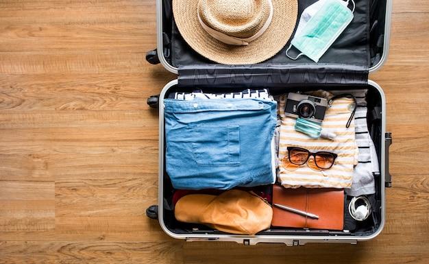 Vista superior del equipaje, maleta con ropa y máscara sobre piso de madera.
