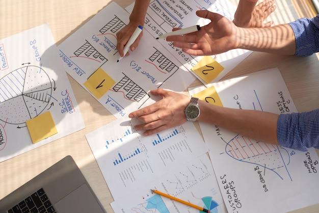 Vista superior del equipo creativo discutiendo gráficos de negocios dibujados en rotuladores