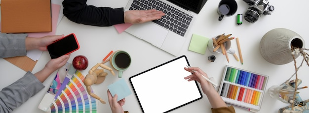 Vista superior del equipo de diseñadores trabajando juntos en un espacio de trabajo mínimo con tabletas, teléfonos inteligentes, computadoras portátiles y suministros de diseño simulados
