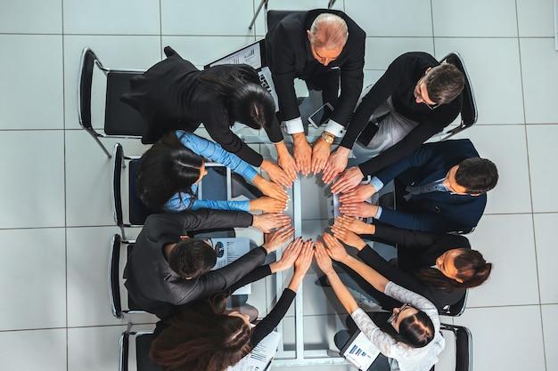 Vista superior. equipo empresarial mostrando su unidad en el lugar de trabajo. el concepto de trabajo en equipo