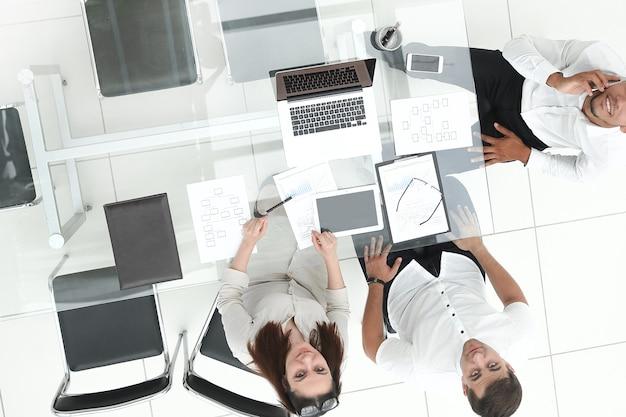 Vista superior. equipo de negocios sentado en el escritorio de la oficina. el concepto de trabajo en equipo