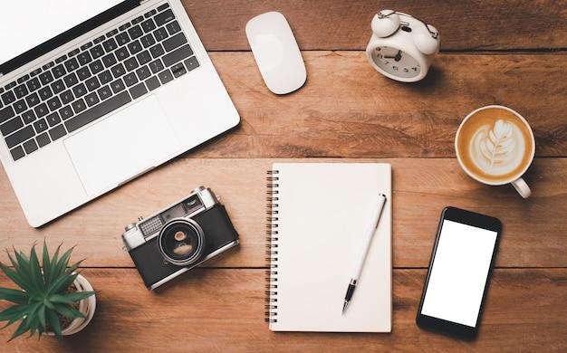 Vista superior equipo de oficina que incluye computadora portátil, teléfono móvil, mouse, computadora portátil, taza de café en el piso de madera