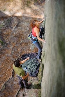 Vista superior del escalador joven atlético escalada empinada pared de roca natural.