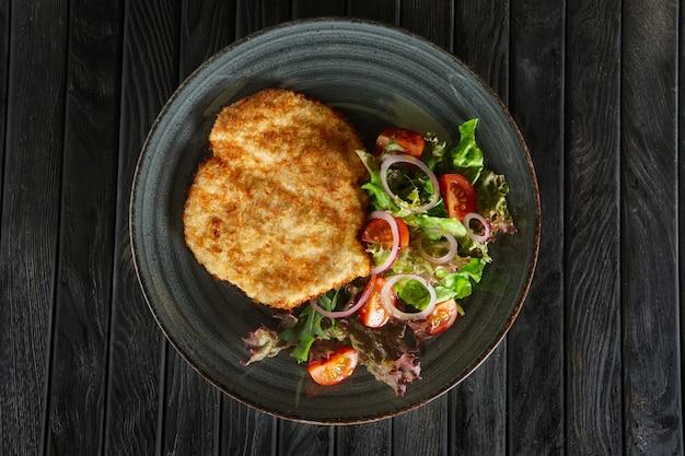 Vista superior de escalope en empanado con verduras frescas y aros de cebolla roja