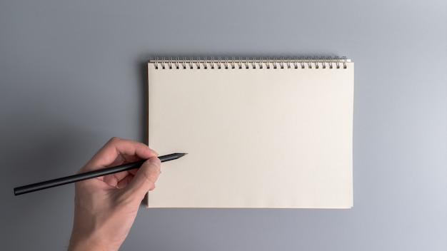 Vista superior de escribir a mano o dibujar en la página del cuaderno en blanco