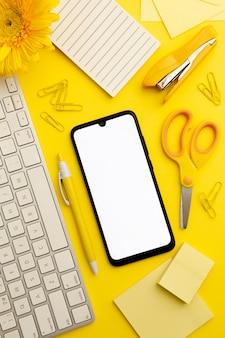 Vista superior escritorio amarillo con teléfono