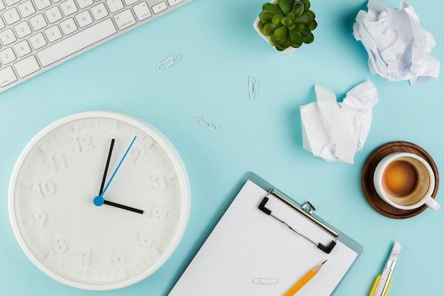 Vista superior del escritorio con bloc de notas y reloj