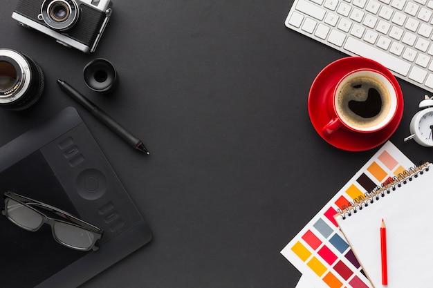 Vista superior del escritorio con café y bloc de dibujo