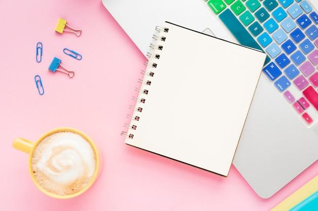 Vista superior del escritorio con cuaderno en blanco
