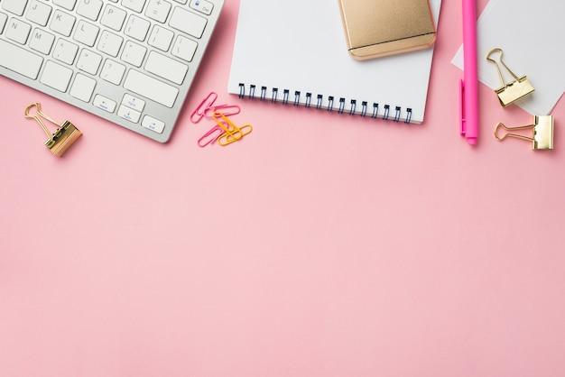 Vista superior del escritorio con cuaderno y clips