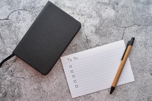 Vista superior del escritorio con cuaderno con una lista de cosas que hacer y lápiz. concepto de estudio en el hogar, planificación y productividad.