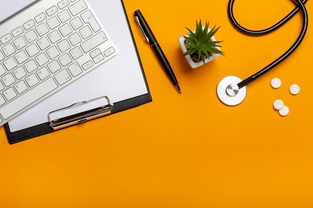Vista superior del escritorio del doctor con el bloc de notas y la pluma del teclado del estetoscopio, prescripción y píldoras