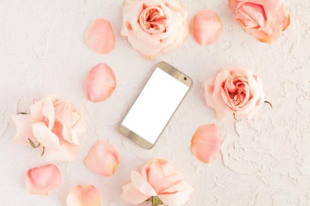 Vista superior del escritorio femenino rosa con moderno teléfono móvil dorado con pantalla en blanco blanco y flores