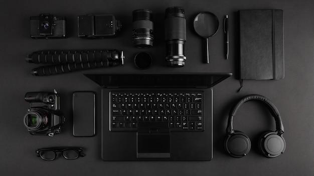 Vista superior del escritorio del fotógrafo moderno con equipo de cámara, computadora portátil y auriculares. tecnología negra oscura y plana. equipo dispuesto sobre la mesa.