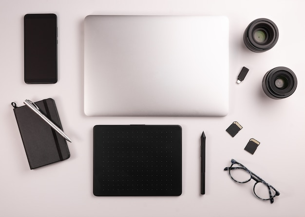 Vista superior del escritorio para fotógrafo o diseñador, con computadora, mesa, café, notebook, móvil, tarjetas de memoria