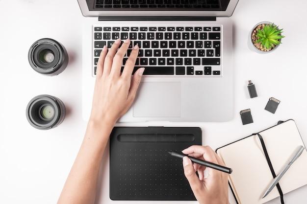 Vista superior del escritorio con laptop, mesa, notebook, tarjetas de memoria.