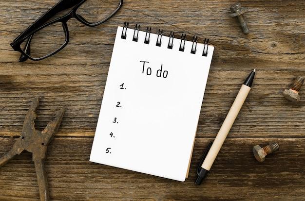 Vista superior del escritorio con lista de tareas en el cuaderno