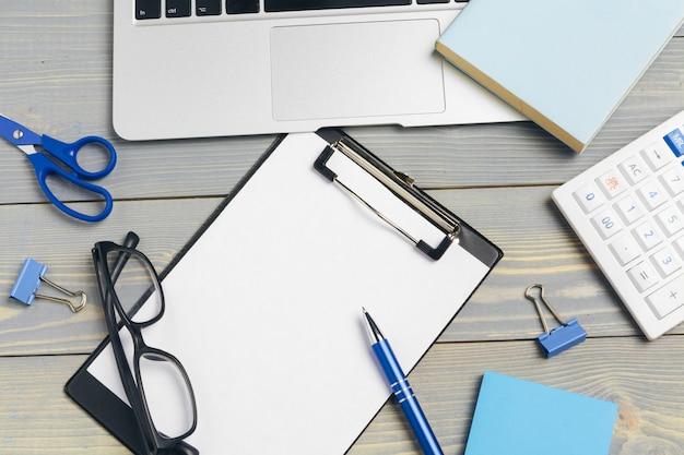 Vista superior del escritorio de madera con gafas y artículos de papelería de cerca. bosquejo