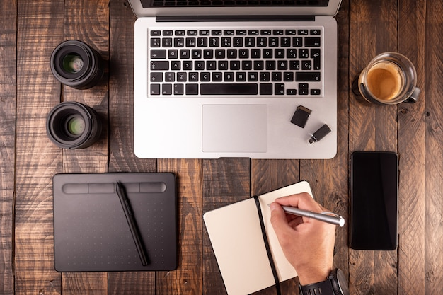 Vista superior del escritorio de madera con laptop, mesa, café, notebook, móvil, tarjetas de memoria.